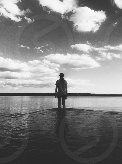 figure wading into water with clouds overhead photo