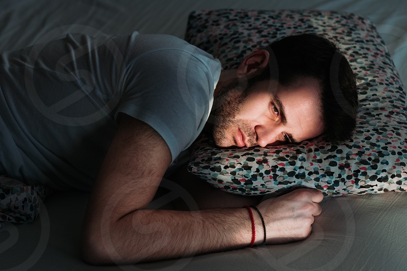 Young depressed man in pain on the bed photo