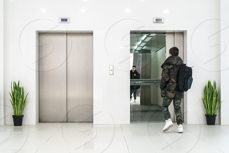 Teenager boy with casual clothes and white sneakers enters in elevator. White contemporary building interior. Flowers in pots and white wall. Metallic elevator doors. photo