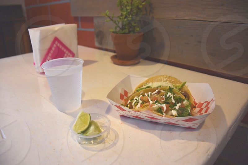 taco on white and red container near white plastic disposable cup photo