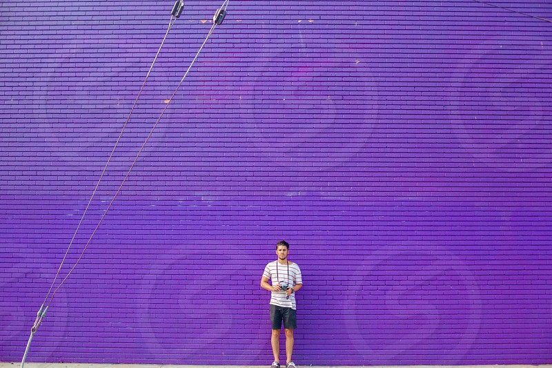 man standing in the front of purple wall photo