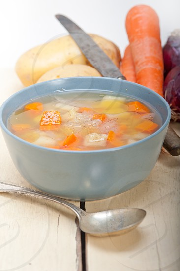 Traditional Italian minestrone soup on a rustic table with ingredients photo