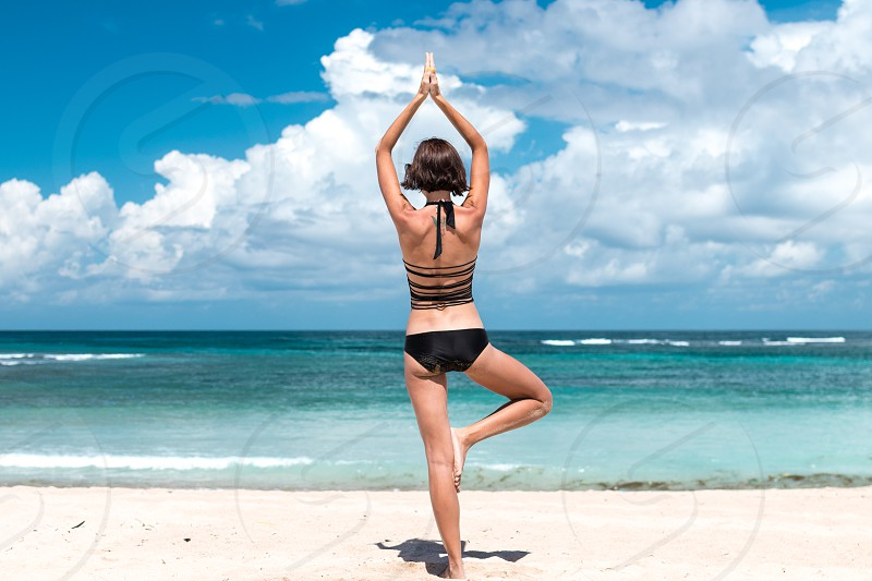 Young healthy attractive woman practicing yoga on the beach Nusa Dua tropical Bali island Indonesia. Free space for text. photo