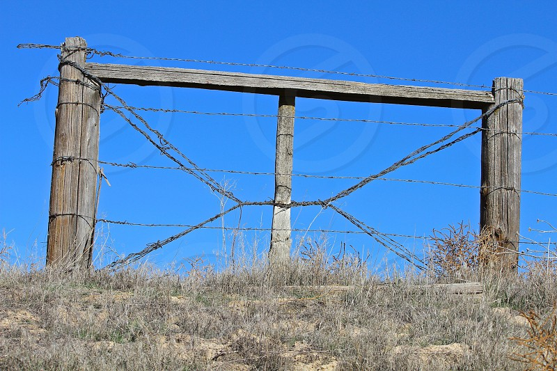 brown wood and barb wire gate on hilltop against blue sky photo
