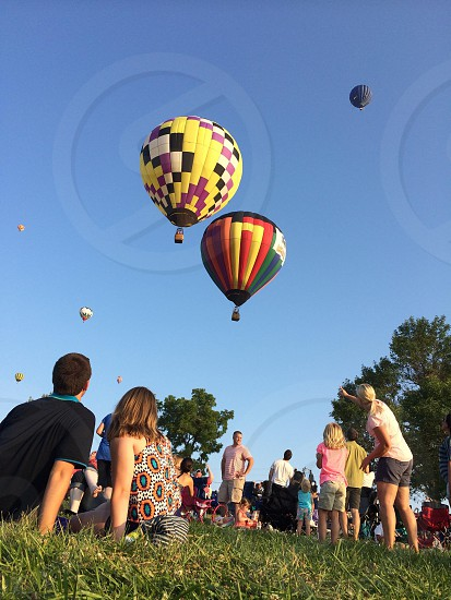 low-angle view of people on a grassy area looking at the hot air balloons in the cloudless blue sky during daytime photo