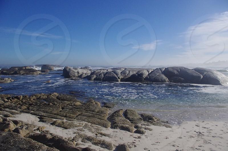 white sand beach with gray rocks photo