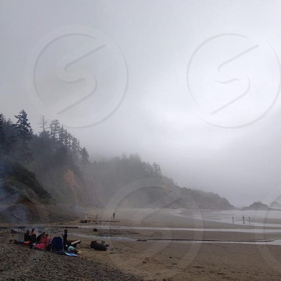 people on sand at foggy beach near cliff covered trees photo