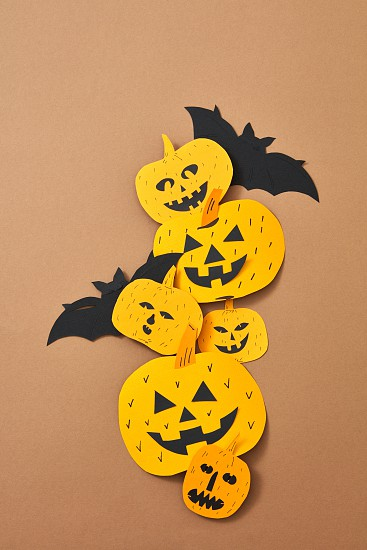 Composition for Halloween handcraft of paper from scary pumpkins and a bat on a brown background with space for text. Flay lay photo