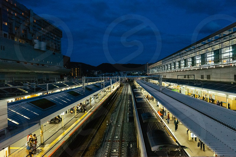 architectural photography of train station with lots of people waiting for the train during nighttime photo