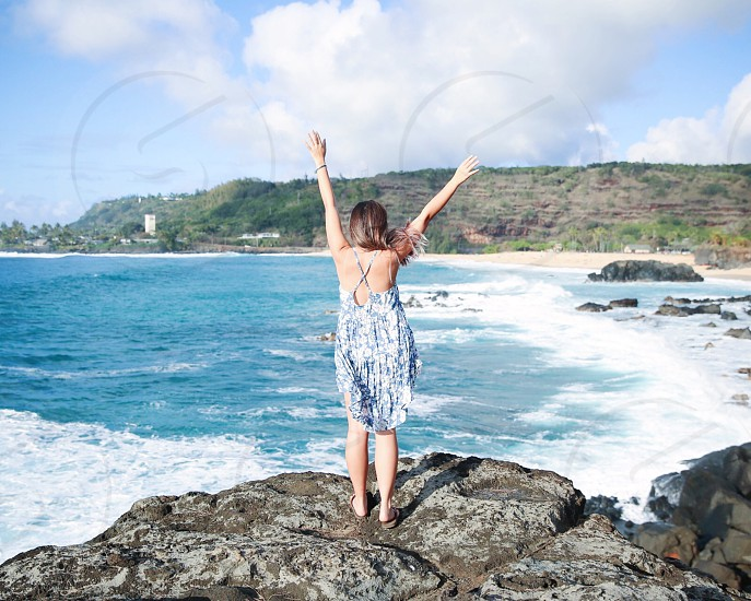 woman in gray and blue cami dress standing in rock beside blue sea during daytime photo