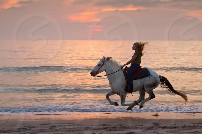 Woman racing along the beach on horseback at sunrise photo