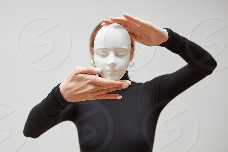 Attractive girl in a black sweater holds gypsum mask sculpture instead of face on a white background place for text. Concept The masks we wear. photo