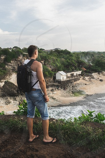 Tourist man with backpak look on picturesque nature view from the cliff photo