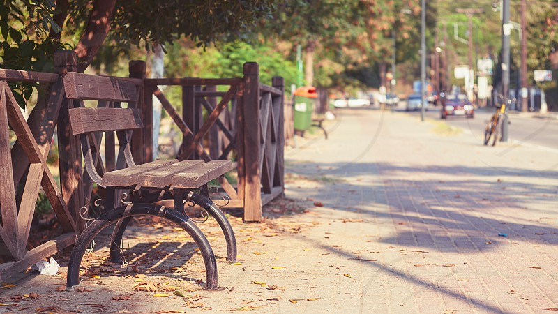 Details of a wooden bench in Stavros town Greece. During summer season street in background.  photo
