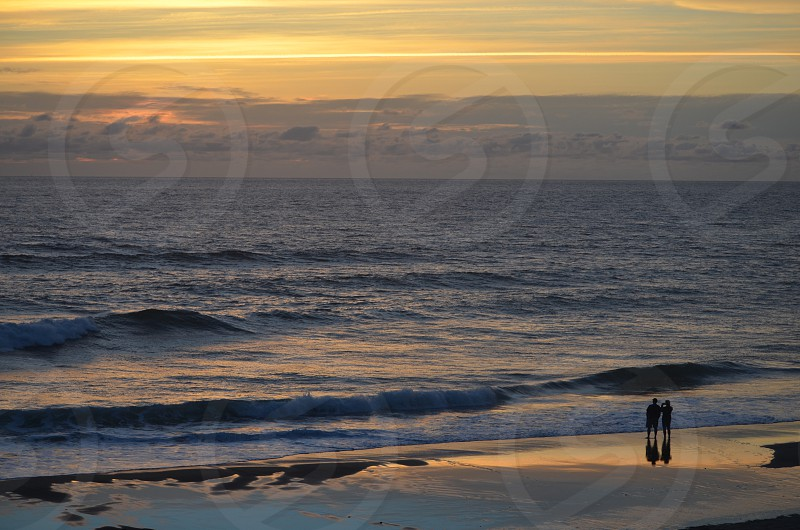 Man & woman watching the sun set in Lincoln City Oregon photo
