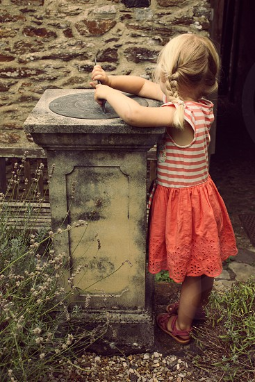 Child playing with sundial in summer dress photo