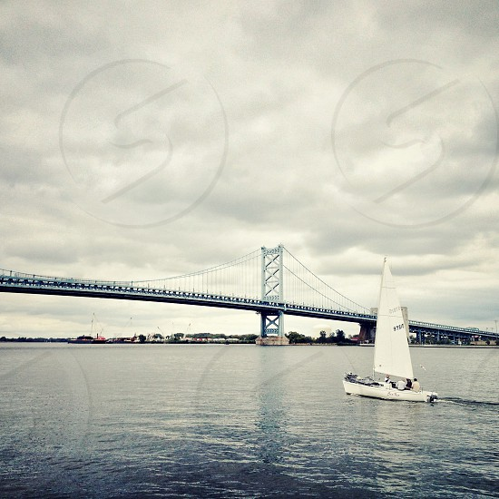 Ben Franklin Bridge and sailboat on the Delaware River as seen from Penn's Landing Philadelphia PA.  philly boat water bridge river sail suspension blue photo