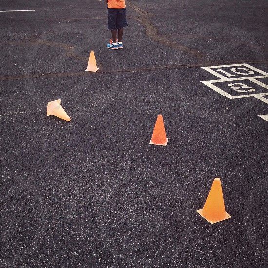 Orange cones blacktop pavement boy legs lead photo