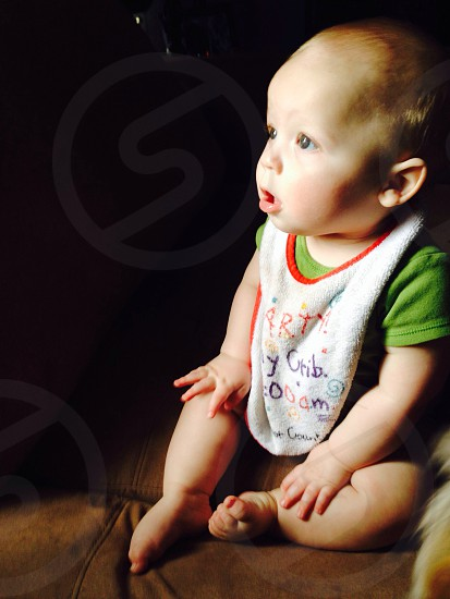 baby in green shirt and white bib photo