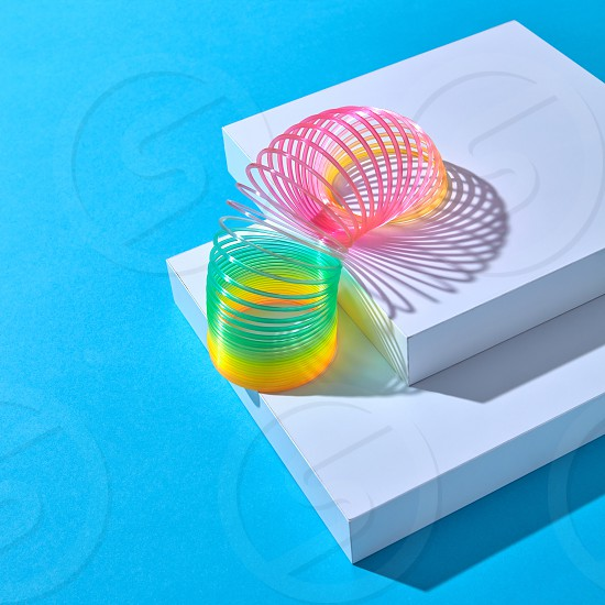 Rainbow plastic multicolored spring spiral goes down white stairs step by step on a pastel background with shadows copy space. photo