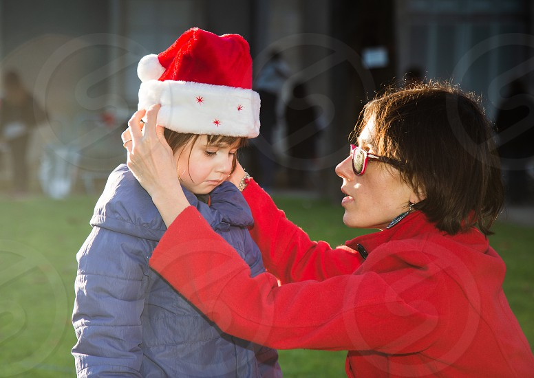 Candid shot of mother consoling her daughter during christmas season . photo