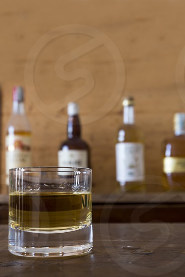 glass with whisky on wooden table photo