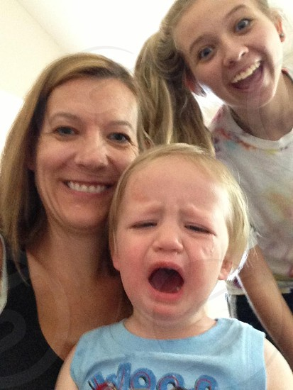 boy crying with 2 women on his back smiling photo