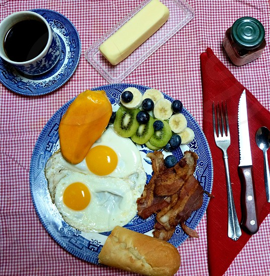 breakfast dinner coffee cream eggs bacon fruit kiwi banana blueberries fork knife spoon silverware cup saucer plate food butter mango baguette napkin cloth photo