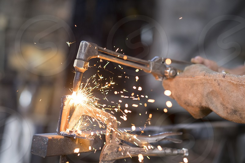 Close up photograph of welding torch causing sparks of burning metal in a shop. photo