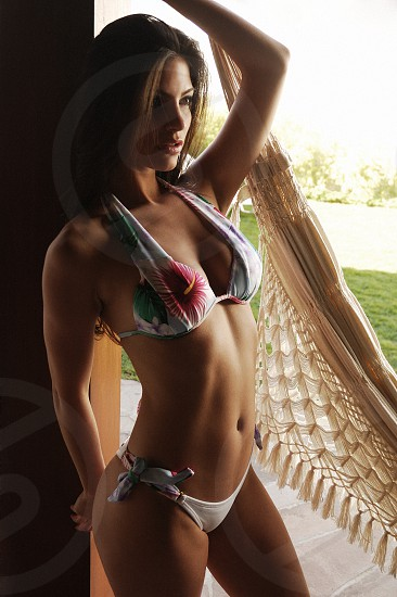 woman in red green and white floral halter bikini standing by brown wooden post and beige hammock photo