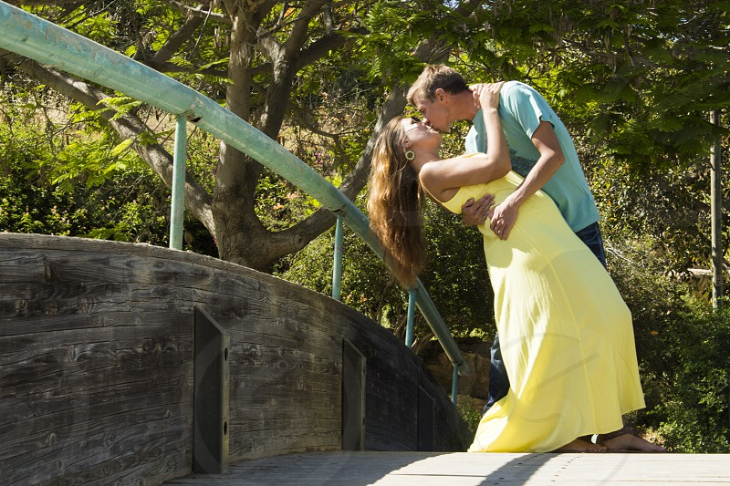 man and woman standing on bridge about to kiss during daytime photo