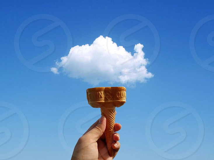 person holding cone with the view of clouds photo