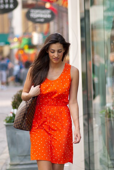 Woman young woman walling outdoor mall caucasian beautiful orange dress polka dots looking down outdoors natural light Southern California summer brown hair long hair  photo