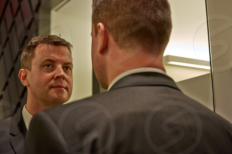 man looking mirror wearing grey suit photo
