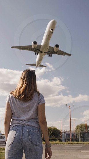 flight sky looking up point of view watch pointing angle low angle girl people from behind traveler travel adventure  photo
