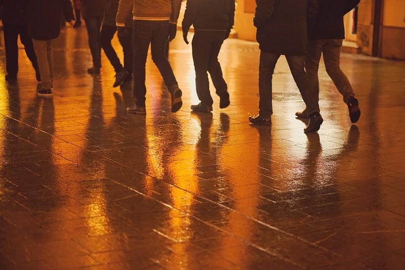 Wet Street Paving and Pedestrian Legs at Night Closeup photo