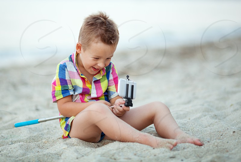 Little laughing boy having fun with smart phone and selfie stick on the beach photo