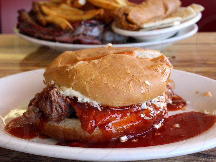 Barbecue beef brisket sandwich with sauce and coleslaw in front of rib and fry plate with tamale and crackers (example from McClard's BBQ Hot Springs AR) Arkansas Food photo
