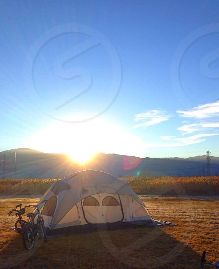 white tent and bikes in front of mountains photo