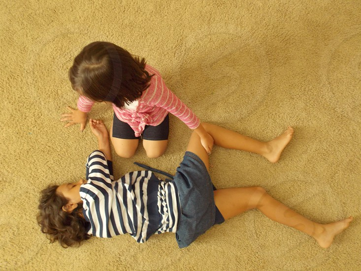 girl wearing a pink striped sweater playing on the floor with a girl wearing a blue striped shirt photo