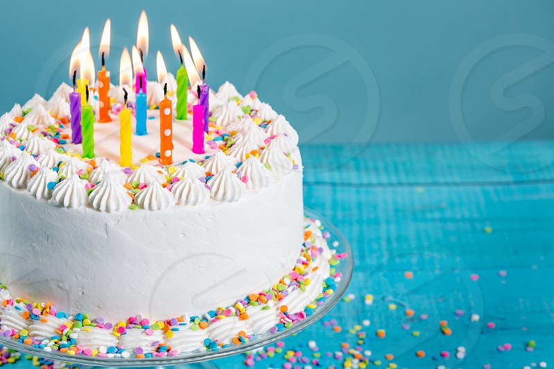 White Buttercream icing birthday cake with with colorful sprinkles and Candles over blue background photo