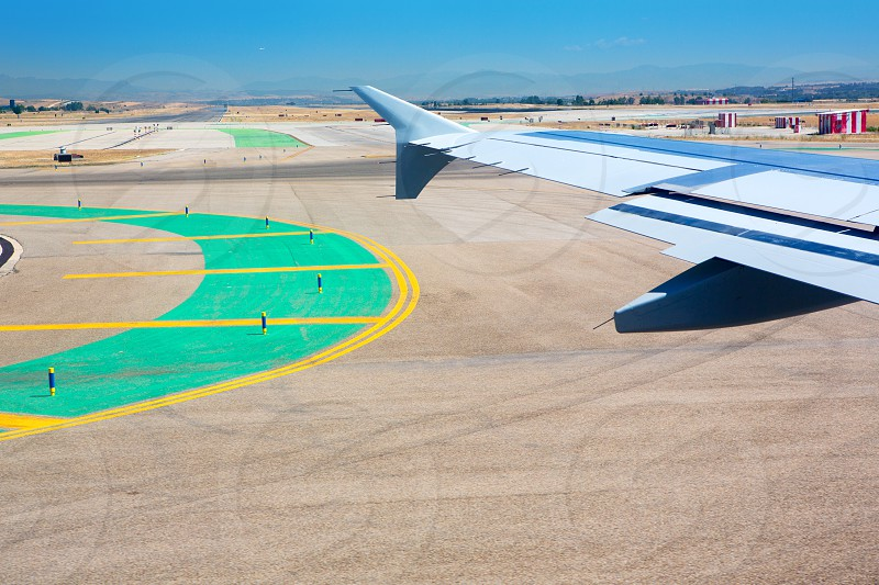 Airplane wing leaving the airport with airstrip road signs photo