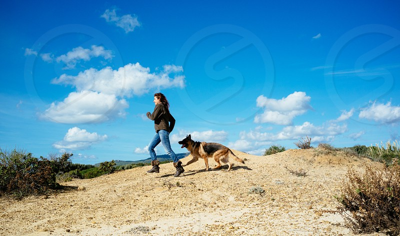Young woman running with her dog. Young woman running with her German Shepherd dog across the sand dunes on a beach against a cloudy blue sky. photo