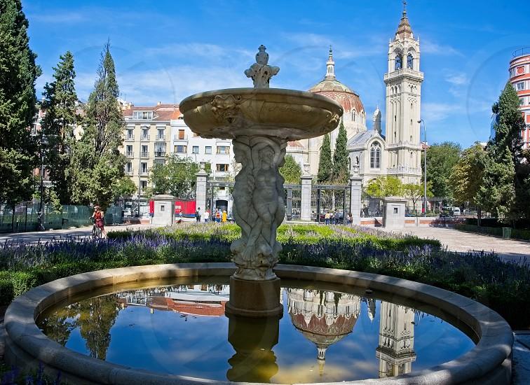 Fountain in El Retiro Park in Madrid and people walking around photo