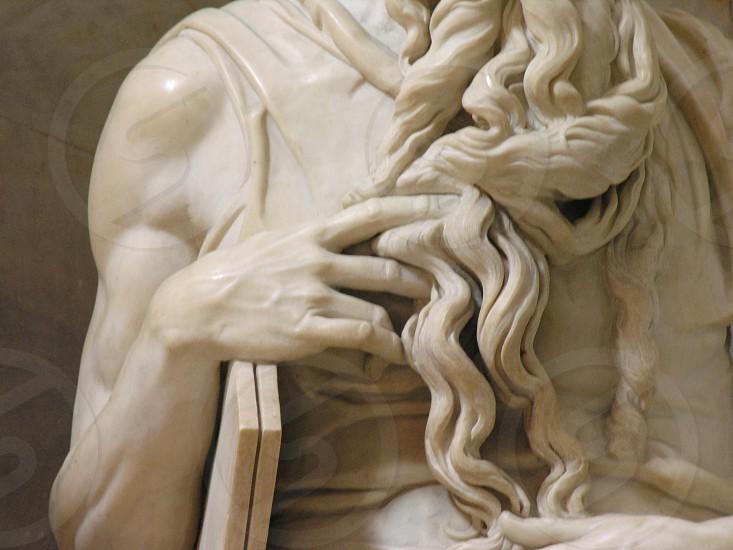 Closeup of Michaelangelo's Moses hand beard veins muscles marble white. photo
