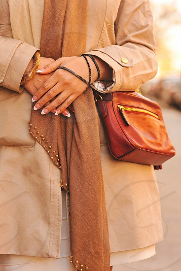 woman in white jacket carrying brown leather sling bag photo