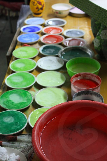 Artists paints multicolored in small bowls spread out on table. Taken just outside of Beijing China. photo