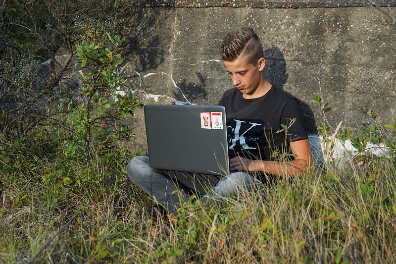 student working on his laptop outdoor photo