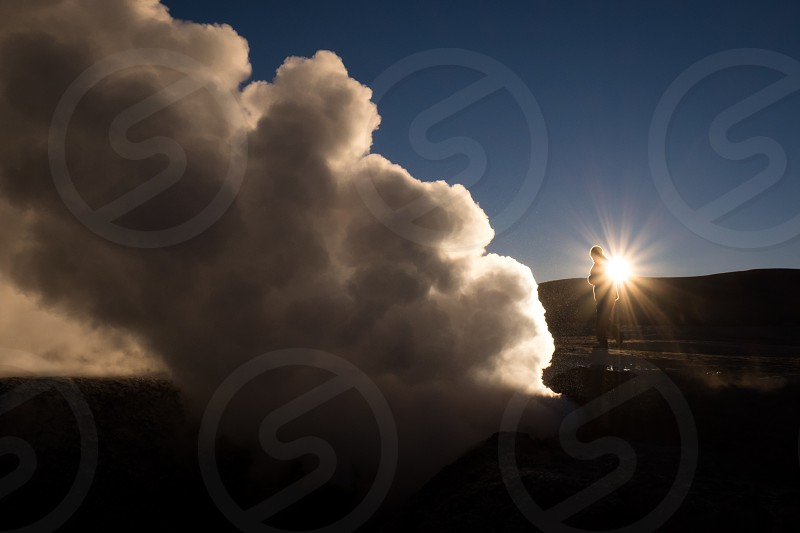 Unidentifiable person and steam from a geyser silhouetted against the sunrise at the high-altitude Sol de Mañana Geyser field in Bolivia. photo