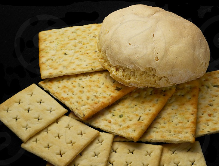 fresh bread and crackers on black background photo